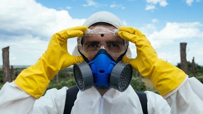 Putting on protective clothing for spraying cotton with pesticides